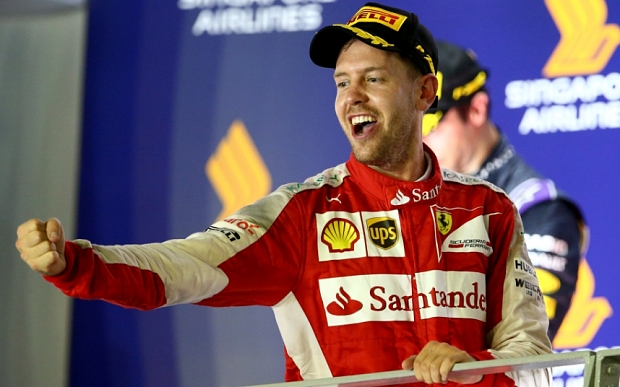 SINGAPORE - SEPTEMBER 20:  Sebastian Vettel of Germany and Ferrari celebrates on the podium after winning  the Formula One Grand Prix of Singapore at Marina Bay Street Circuit on September 20, 2015 in Singapore.  (Photo by Clive Rose/Getty Images)